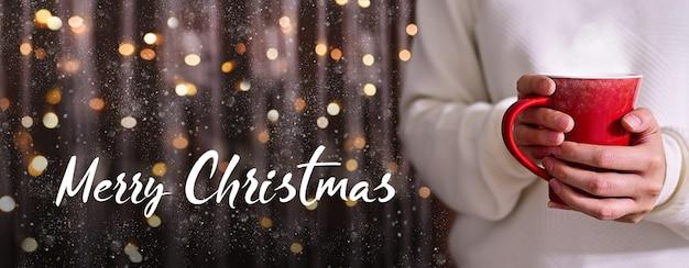 メリークリスマスの女性の手が赤いカップで熱いコーヒーを保持している光のボケ味のきらめきの背景