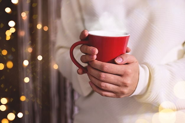 メリークリスマスの女性の手が赤いカップでホットドリンクを保持している光のボケ味のきらめきの背景