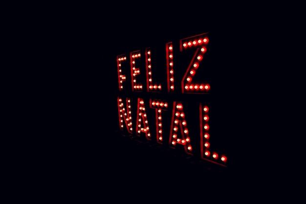 네온 레드 라이트에 포르투갈어로 작성된 메리 크리스마스. 크리스마스 검정색 배경, 텍스트를 위한 공간입니다.