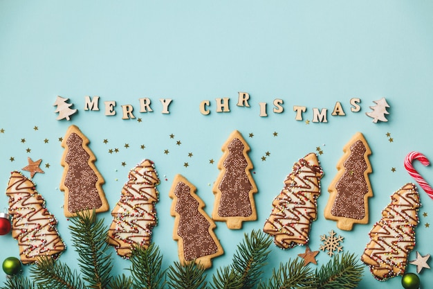 Merry christmas written with wooden letters, cookies and christmas decorations