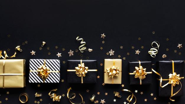 メリークリスマス、クリスマス、新年のお祝いのコンセプト、ギフトボックスと暗い背景に金色の飾り。冬の季節と記念日