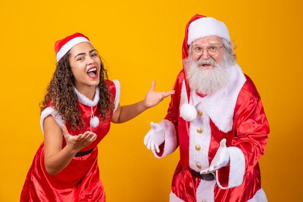 メリークリスマス。黄色の背景で遊んで相互作用する若いnoeleteと本物のサンタクロース
