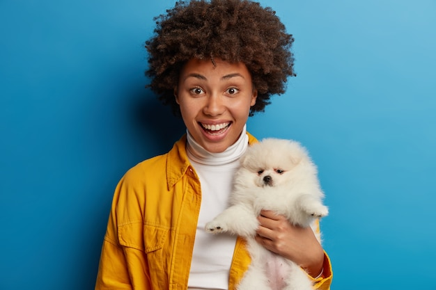 Merry ethnic woman with afro hairstyle glad to save life of homeless puppy, holds white spitz closely to herself, being on way to veterinary healthcare clinic