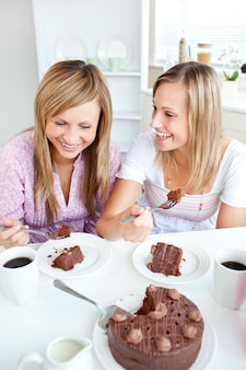 Merry female friends eating a chocolate cake in the kitchen