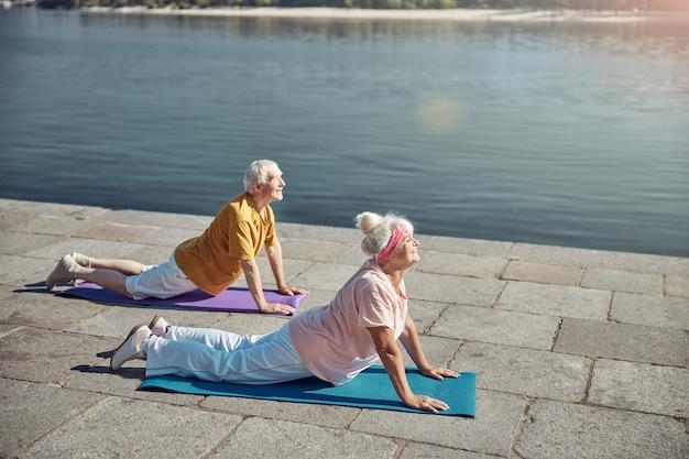上向きの犬の運動を行う陽気なフィットの年配の女性と彼女の笑顔の夫
