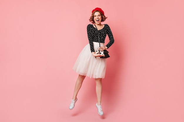 Веселая французская молодая женщина танцует на розовом фоне. вид в полный рост кудрявой девушки в пышной юбке, выражающей счастье.