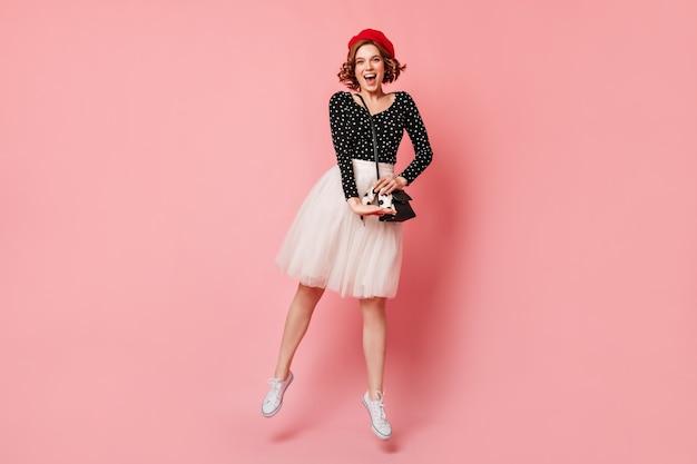 Allegra giovane donna francese che balla su sfondo rosa. vista integrale della ragazza riccia in gonna lussureggiante che esprime felicità.