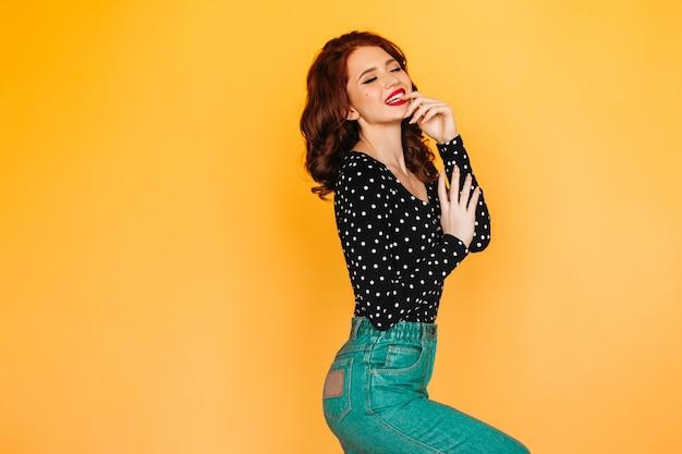 目を閉じて笑っている緑のジーンズの陽気な生姜の女の子。黄色い空間で踊るインスピレーションを得た巻き毛の女性のスタジオショット。