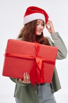 Веселая девочка новый год красный подарок шляпа санта-клауса рождество. фото высокого качества