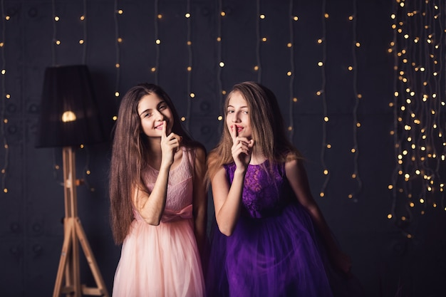 陽気なガールフレンド。ピンクと紫のドレスを着た2人の女の子がshhを示しています