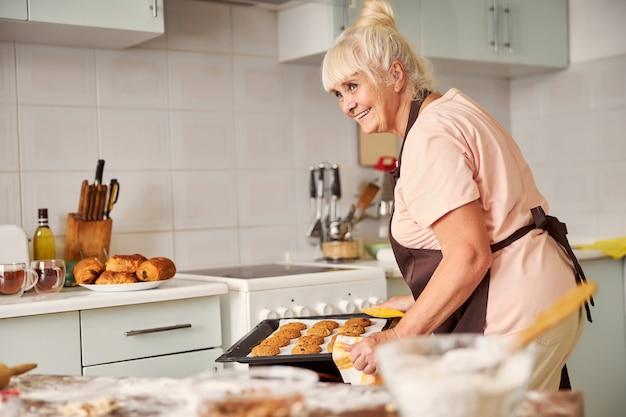 オーブンから新鮮なクッキーを取り出している陽気な祖母