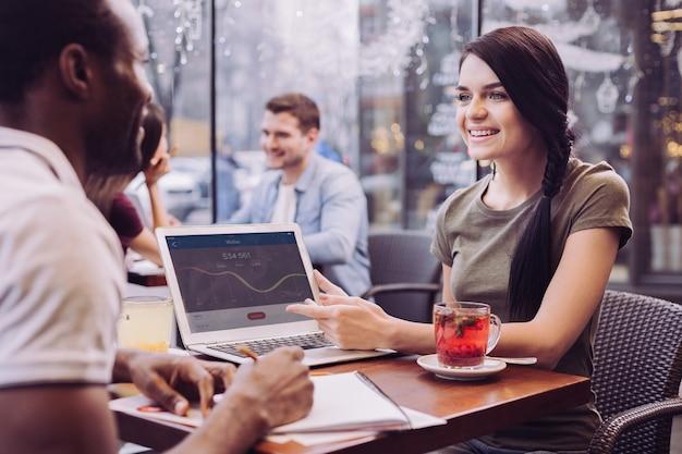 여자가 웃고 남자를 응시하는 동안 카페에서 토론하는 메리 좋은 두 동료