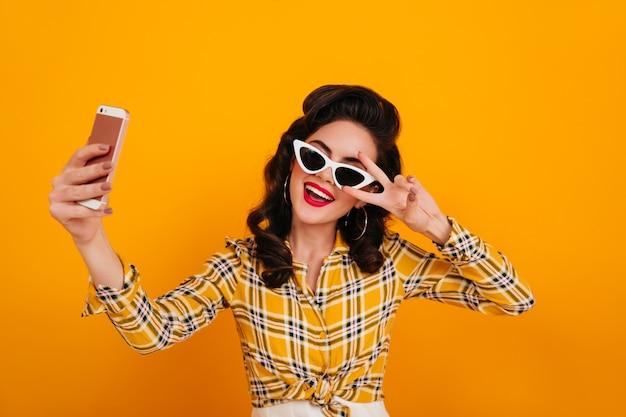 Веселая девушка кинозвезды позирует со знаком мира на желтом фоне. студия сняла радую женщину в клетчатой рубашке, делающей селфи.