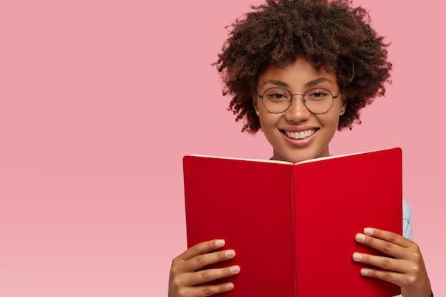 Веселая довольная афроамериканка с довольным выражением лица, носит оптические очки для хорошего зрения, держит учебник, изучает материал для семинара, изолирована на розовой стене с пустым пространством слева