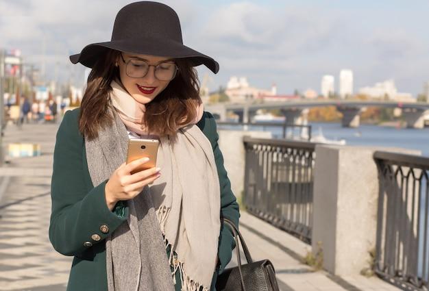 携帯電話を使用してファッショナブルな服を着た眼鏡と帽子の陽気な笑顔のブルネットの女性