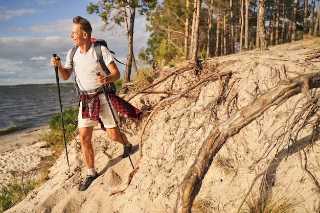 Merry sporty mature man is going nordic walking with backpack in forest near sea shore
