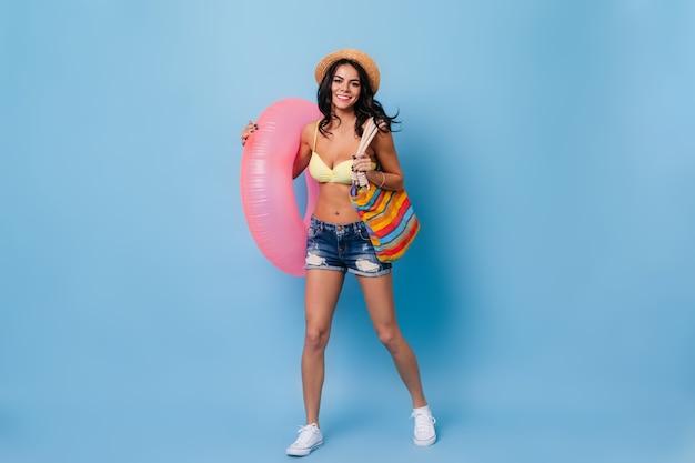 青い背景で踊るデニムのショートパンツで陽気な日焼けした女性