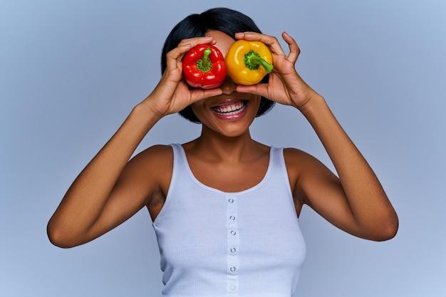 Веселая женщина, пряча глаза за красными и желтыми перцами. концепция диеты