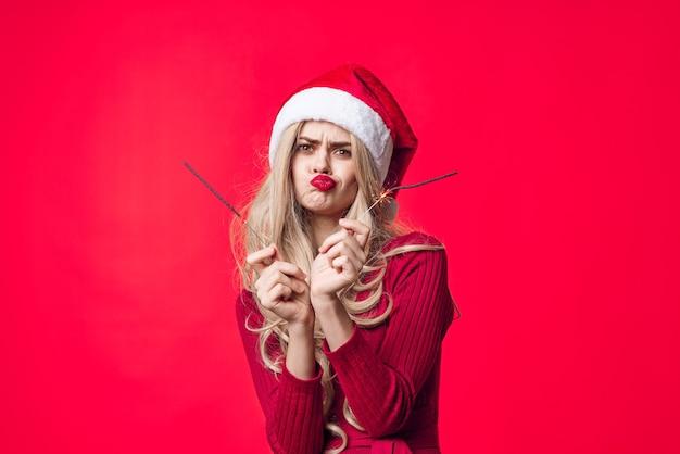 サンタ帽子線香花火クリスマス赤い背景の陽気な女性。高品質の写真