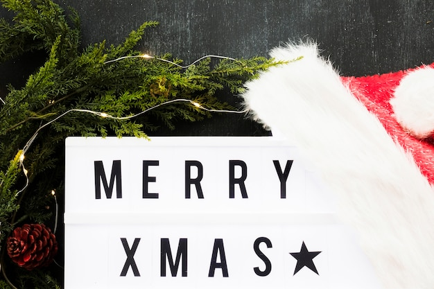 Merry xmas inscription on board with santa hat and branches
