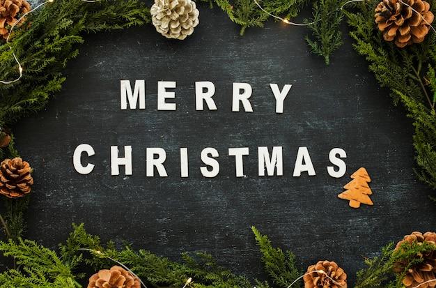 Веселая рождественская надпись с конусами на столе