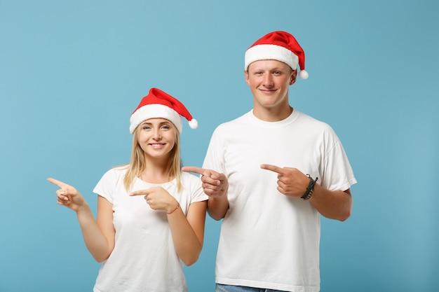 クリスマスの帽子のポーズで陽気な若いサンタカップルの友人の男と女