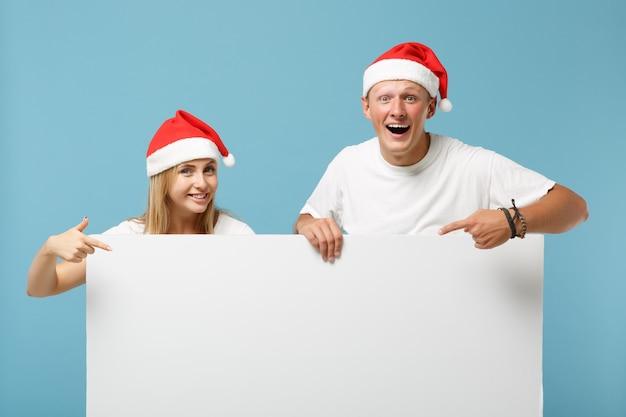 クリスマスの帽子の陽気な若いサンタカップルの友人の男と女
