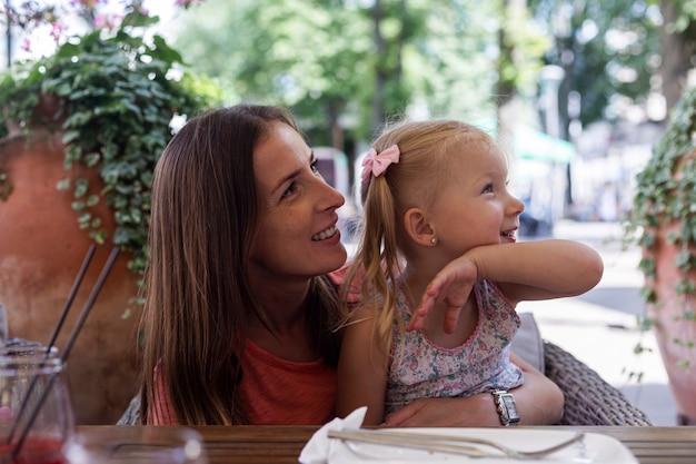 명랑한 젊은 여성과 카페테리아의 테이블에 앉아 있는 어린 소녀.