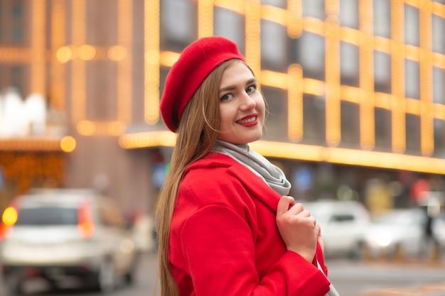 ストリートフェアで歩く赤いコートを着た陽気な若い女性