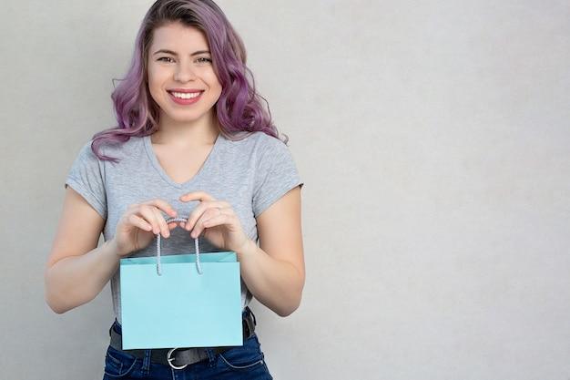 ギフトバッグを保持している紫色の髪の陽気な若い女性、灰色の背景にスタジオ撮影。空きスペース