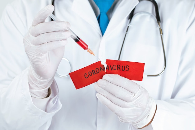 Понятие о коронавирусном карантине. mers-cov.novel коронавирус (2019-ncov) .covid-19, доктор со шприцем, содержащим коронавирусную вакцину. разорвите красную бумагу словом коронавирус.