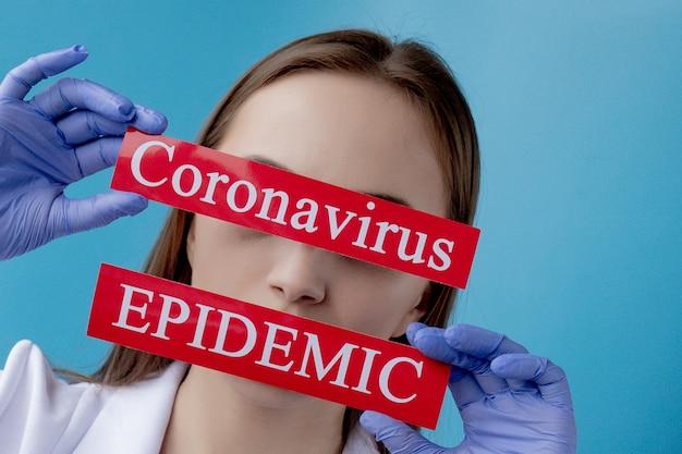 青色の背景にmesaageコロナウイルスと赤い紙を指している医師の女性。世界保健機関whoがコロナウイルス病の新しい公式名covid-19を発表