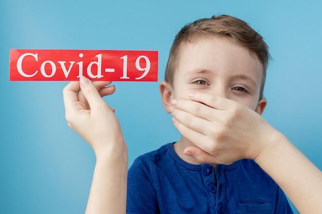 青色の背景にmesaageコロナウイルスと赤い紙を指している小さな男の子。世界保健機関whoがコロナウイルス病の新しい正式名称をcovid-19と発表