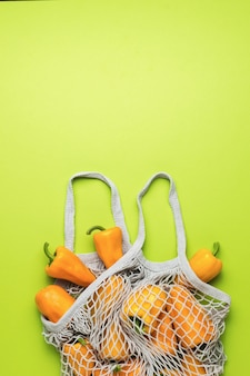 A mesh bag filled with orange bell pepper on a green background. vegetarian food.