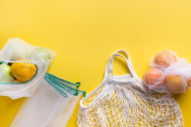 Mesh bag with fruits on yellow.