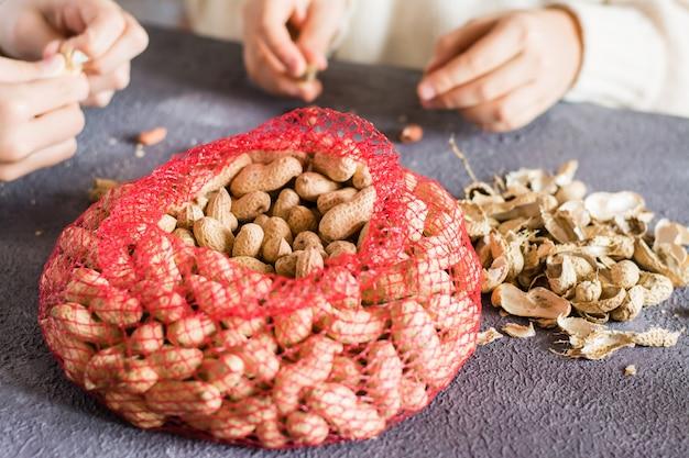 殻付きピーナッツと2人の女の子を背景にしたメッシュバッグがテーブルでナッツをはがしています。ライフスタイル