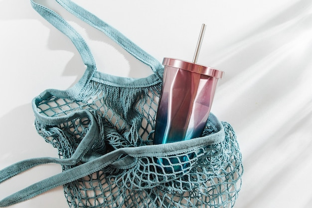 Mesh bag with reusable metal water bottle and cup on white background.