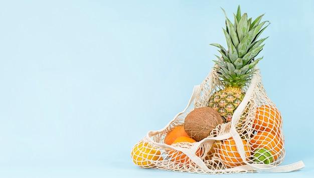 밝은 파란색 배경에 열대 과일이 있는 메쉬 가방