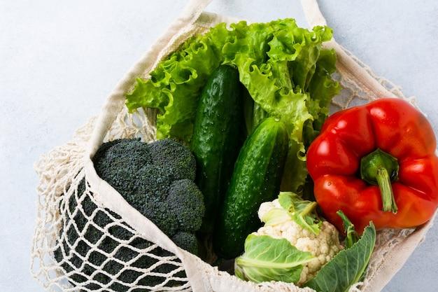 야채와 함께 메쉬 가방. 제로 폐기물 및 건강 채식주의 자 및 채식주의 자 음식 개념. 공간을 복사하십시오.