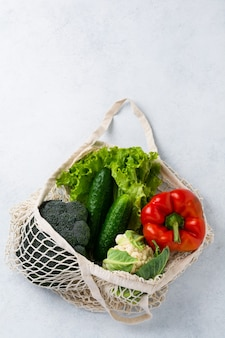 야채가 든 메쉬 백. 제로 폐기물 및 건강 채식주의 자 및 채식주의 자 음식 개념.