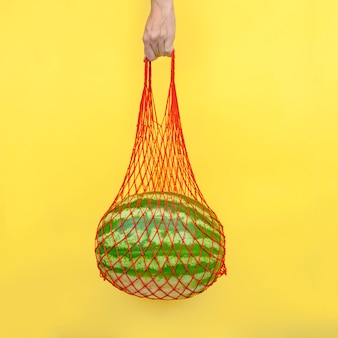 Mesh bag with a watermelon in hand on a yellow background