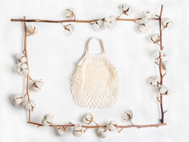 白い背景の上の綿の花の枝で作られたフレーム内のメッシュバッグ。平置き