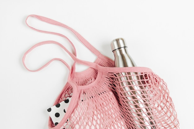 Mesh bags with reusable metal water bottle and books on white background.