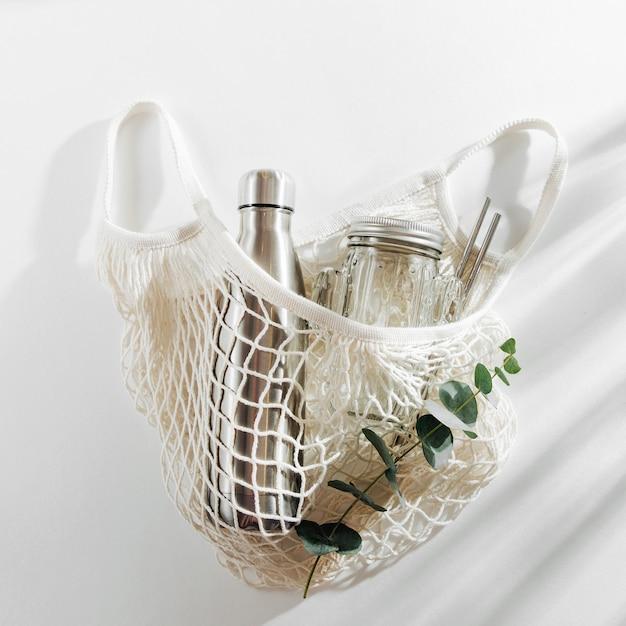 흰색 배경에 재사용 가능한 금속 물병이 있는 메쉬 가방. 지속 가능한 라이프 스타일.