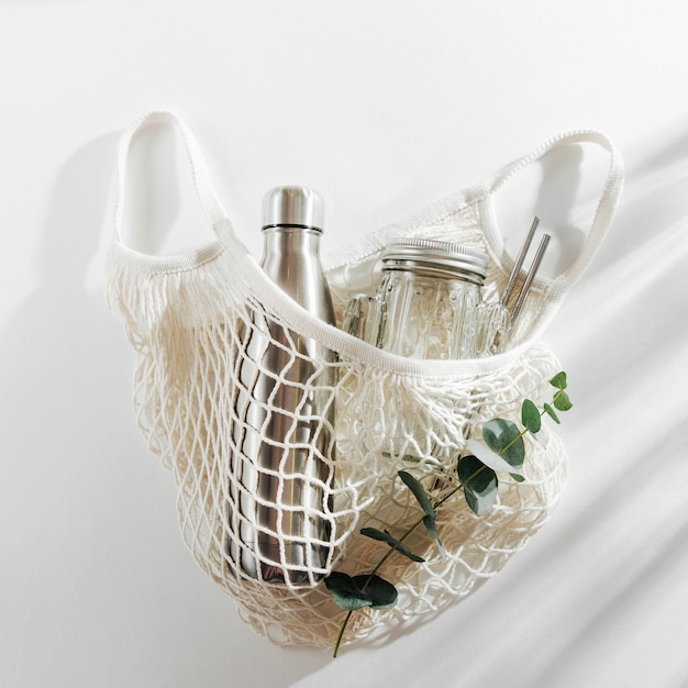 Mesh bags with reusable metal water bottle on white background. sustainable lifestyle.