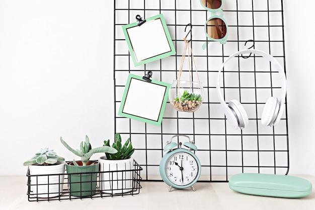 ブランクカード、サングラス、イヤホン、観葉植物、目覚まし時計付きメッシュボード。家にいる、家の組織、計画のコンセプト。