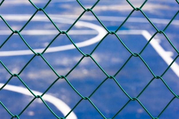 Сетчатая перегородка стадиона, зеленая сетка из стали и пластика, барьер между стадионом и внешней стороной