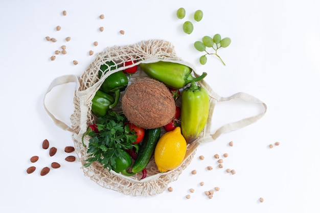Mesh grocery bag full of healthy food on white background from above
