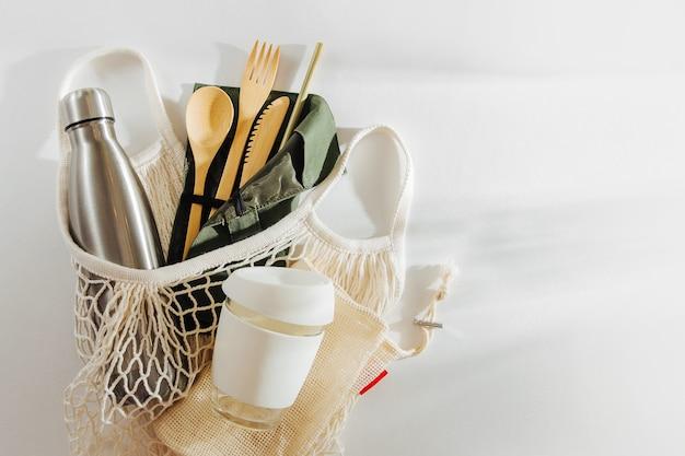 竹製カトラリー、再利用可能なコーヒーマグ、ウォーターボトルが付いたメッシュマーケットバッグ。