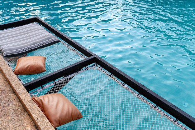 Mesh seat with pillows jut out on swimming pool